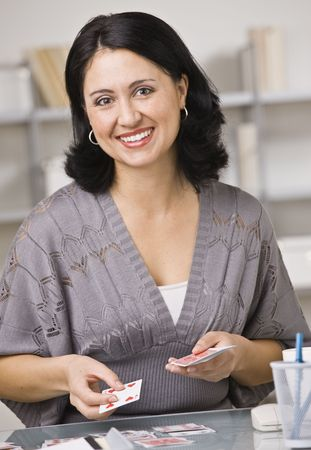 A young woman is playing with playing cards and smiling at the camera.  Vertically framed shot. photo
