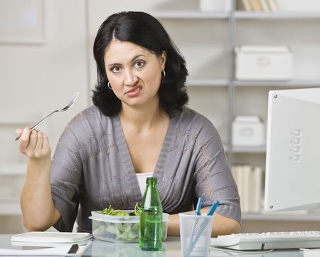 midlife: A young woman is eating lunch in her office.  She is looking at the camera.  Horizontally framed shot. Stock Photo