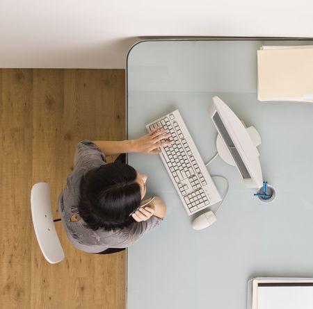 Una mujer de negocios está sentada en un escritorio en una oficina. Ella está trabajando en una computadora y mirando a la pantalla. Disparo Plaza enmarcada. Foto de archivo - 5334082