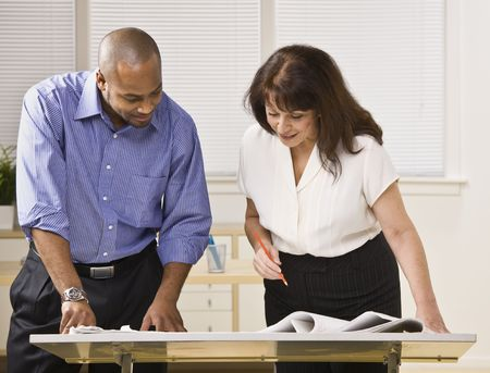 A businessman and woman are working together in an office.  They are looking away from the camera.  Horizontally framed shot. photo
