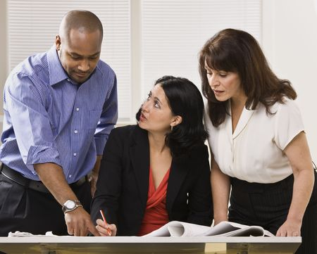 A group of business people are in an office and are looking at some paperwork.  They are talking and looking away from the camera.  Horizontally framed shot.