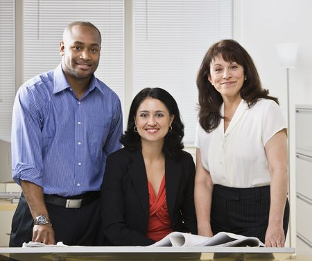 Business team posing for picture, Two white woman and one african american man standing at desk.Horizontal photo