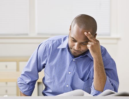 Attractive African American male sitting at desk looking at drawings. Horizontal Stock Photo - 5334074