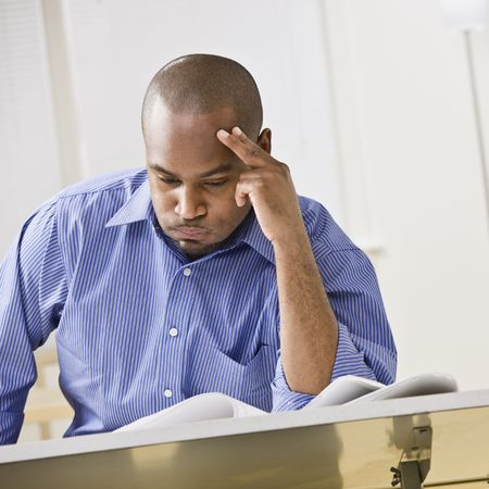 bored student: An attractive African-American male studying at a desk. He is resting his head against his fingers, and is puffing his cheeks out with air.  Square composition.