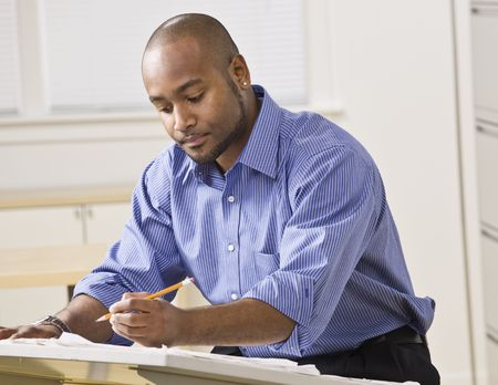 Een jonge zakenman werkt op sommige blauwdrukken in een kantoor. Hij kijkt weg van de camera. Horizontaal ingelijste foto. Stockfoto