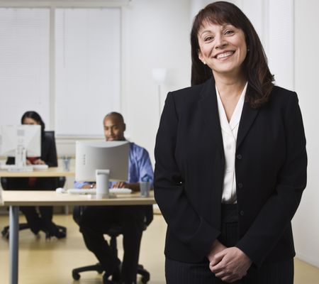 office desk: A businesswoman is standing in an office while her coworkers are seated at computer desks.  She is smiling at the camera.  Horizontally framed shot.