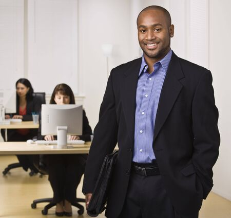 horizontally: A young businessman is standing in an office with some other business people.  He is smiling at the camera.  Horizontally framed shot. Stock Photo