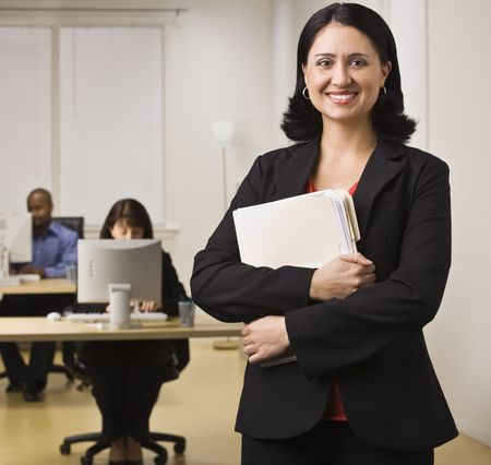 An attractive brunette is holding file folders and is smiling at the camera.  She is dressed in business attire and appears to be at her place of employment.  There are people working on computers at the desks behind her.  Square composition. Stock Photo
