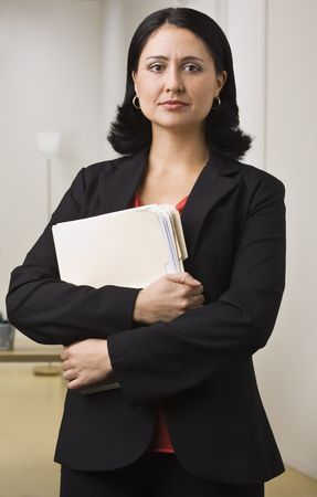 A businesswoman is standing in an office holding some paperwork.  She is looking at the camera.  Vertically framed shot. photo