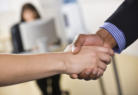 A businessman and woman are shaking hands in an office.  Horizontally framed shot. photo