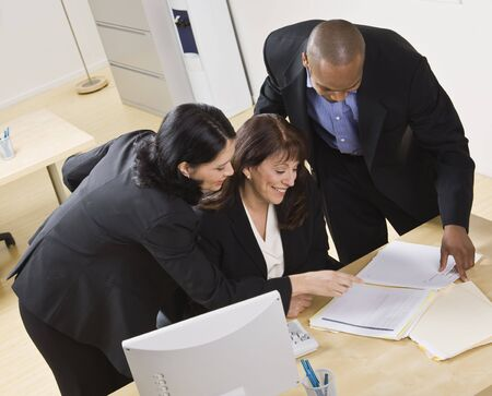 sitting down: A group of business people are working together in an office. They are looking at paperwork.  Horizontally framed shot.