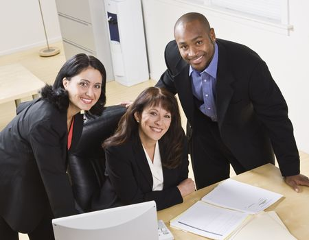 A group of business people are working together in an office.  They are smiling at the camera.  Horizontally framed shot.