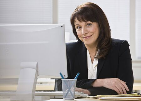Attractive business woman stting at desk behind computer monitor smiling at camera. Horizontal. Stock Photo - 5333804