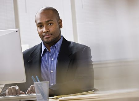 A young businessman is working on a computer in an office.  He is smiling at the camera.  Horizontally framed shot.
