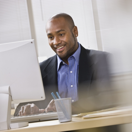 working on computer: Attractive African American smiling at computer, while sitting at a desk typing on keyboard. Square.