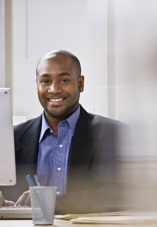 A young businessman is seated at a desk in front of a computer, and is smiling at the camera. Vertically framed shot. Stock Photo - 5333529