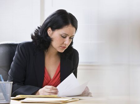 A young, attractive woman is looking over some paperwork on a desk.  She is looking away from the camera.  Horizontally framed shot. photo