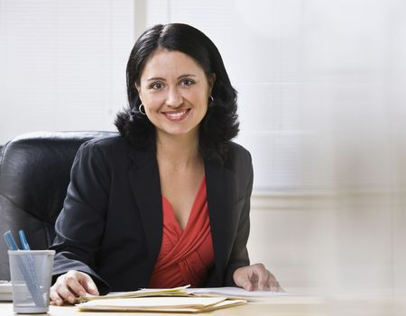 A young businesswoman is seated at a desk in an office and is smiling at the camera.  Horizontally framed shot.