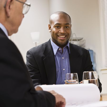 Two businessmen are in a meeting at an office.  The younger man is smiling at the camera.  Square framed shot. Stock Photo - 5333408