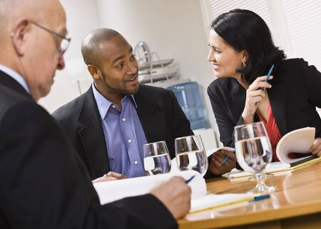 Three attractive business people sitting at a table with water and paperwork. Horizontal photo