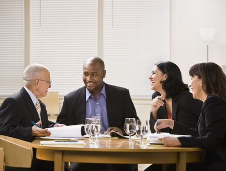 laughs: A group of business people are in a meeting in an office.  They are talking and laughing and looking away from the camera.  Horizontally framed shot.