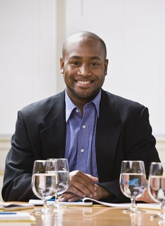 African American male sitting at desk with water, smiling at the camera. Vertical Stock Photo - 5333631
