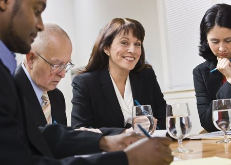 A group of business people are seated around a desk in a meeting.  They are looking away from the camera.  Horizontally framed shot. photo