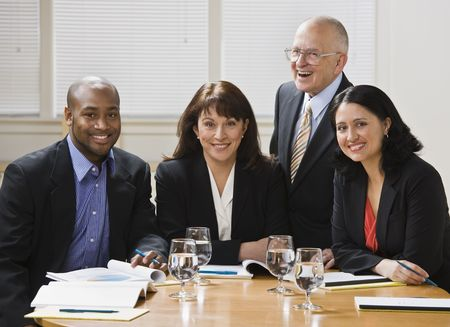 Four business workers, two men and two women, sitting at desk smiling at camera. Horizontal