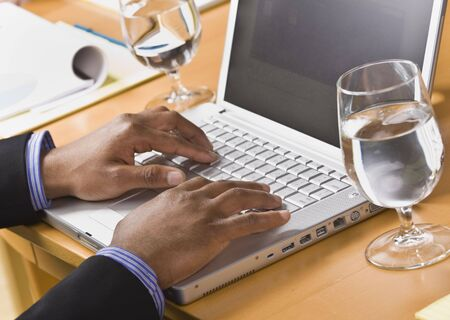 African American male hands typing on laptop keyboard. Glass of water on desk. Horizontal photo