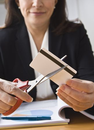 A businesswoman is cutting up a credit card with a pair of scissors.  Vertically framed shot. photo