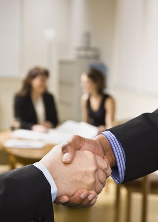 Two businesspeople are shaking hands in an office.  Two office ladies are seated at a desk in the background.  Vertically framed shot. photo