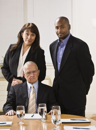 Three business people posing for photo. African American male and woman standing, male senior sitting in front of them. Vertical.
