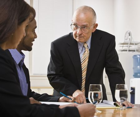 Senior male, african American male and white female meeting at desk. Senior male speaking, other listening. Horizontal photo