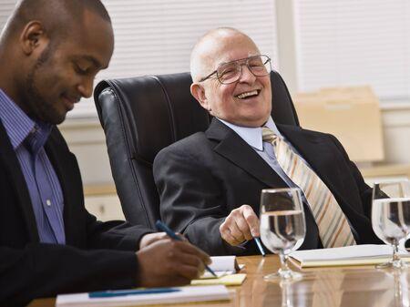 老人と若いビジネスマンは、オフィスで机に着席しています。彼らは笑いと、カメラから離れて探しています。水平方向にフレームのショット。 写真素材