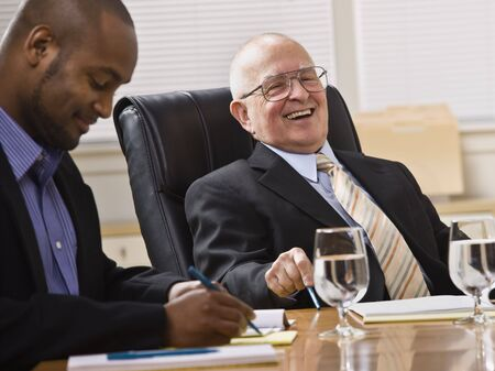 sitting down: An elderly man and a young businessman are seated together at a desk in an office.  They are laughing and looking away from the camera.  Horizontally framed shot.