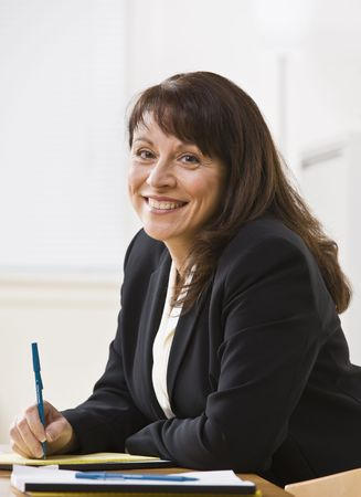 midlife: A businesswoman is seated at a desk and is smiling at the camera.  Vertically framed shot.