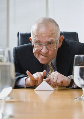 flicking: Playful senior male sitting at desk flicking paper football. Vertical