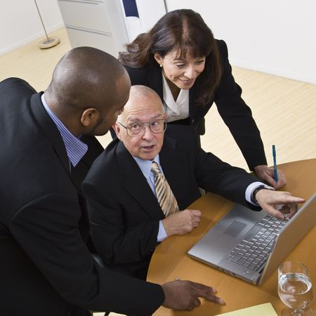 A group of business people are working on a laptop in an office.  The elderly man is speaking to and looking at the younger man, and the young woman is looking at the computer screen.  Square framed shot.