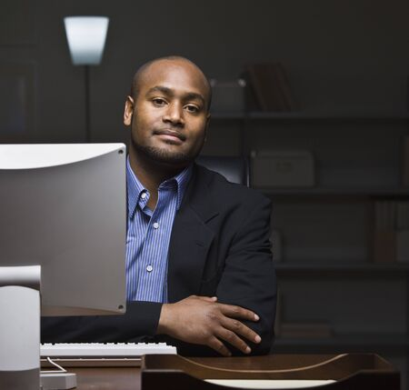 A young businessman is seated at a desk and is working on a computer.  He is looking at the camera.  Square framed shot. Stock Photo
