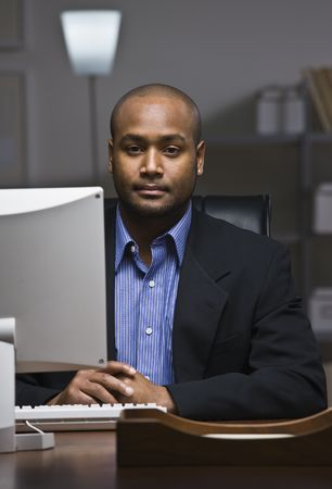 A young businessman is working on his computer at the office.  He is looking at the camera.  Vertically framed shot. photo