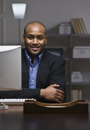 African American business man smiling at camera, sitting at desk with computer monitor. Vertical photo