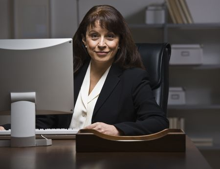Attractive businesswoman sitting at desk in suit, behind monitor. Looking at camera. Horizontal