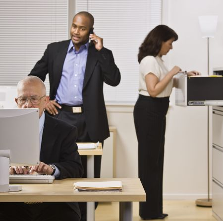 Two businessmen and woman are working in an office.  The elderly man is on a computer, the younger man is talking on a cell phone and the woman in looking through a filing cabinet drawer.  Square framed shot. photo
