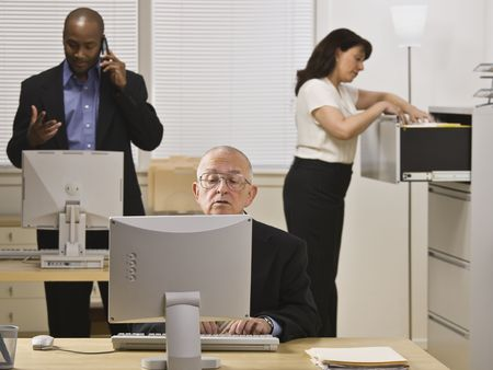 A group of business people are working in an office.  Horizontally framed shot. photo