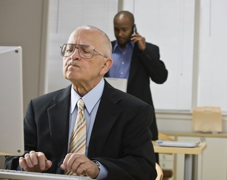 midlife: Two businessmen are working in an office.  The older man is working on a computer and the younger man is talking on a cell phone.  Horizontally framed shot.