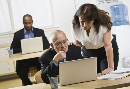 midlife: A group of business people are in an office and are working on computers.  They are looking away from the camera.  Horizontally framed shot. Stock Photo
