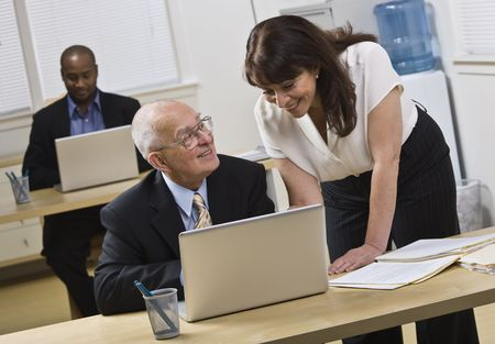 business attire teacher: Attractive woman standing over older man helping him with laptop. African American male in back. Horizontal.