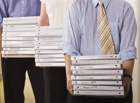 A group of business people are holding binders in an office.  Horizontally framed shot. photo