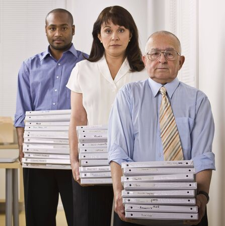 Three Business People are standing in an office, holding binders, and looking at the camera.  Square framed shot. photo