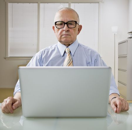 An elderly businessman is working on a laptop in an office.  He is looking at the camera.  Square framed shot.